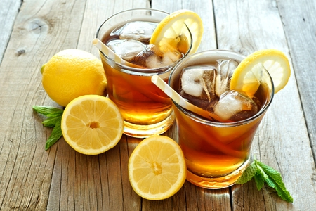 Two glasses of cold iced tea with lemon slices on a rustic wood background Stockfoto