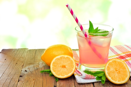a straw: Glass of cold pink lemonade with lemon slices and mint, on wood with outdoors background Stock Photo