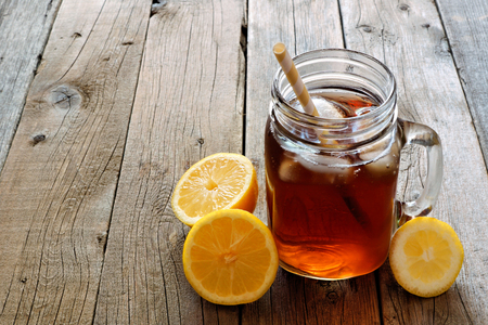 Mason jar glass of cold iced tea with lemon slices on a rustic wood background Stock fotó