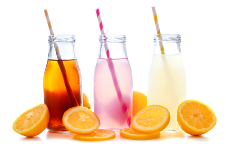 Iced tea, pink lemonade and lemonade summer drinks in bottles with straws and lemon slices isolated on white Stock Photo