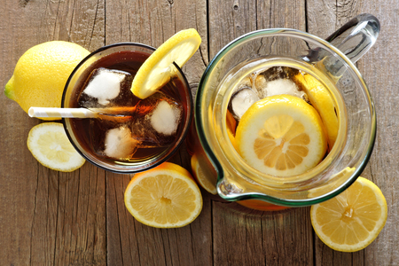 flavoured: Pitcher and glass of iced tea with lemon slices, downward view on a rustic wood background
