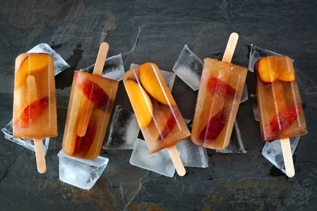 Group of peach iced tea popsicles with ice on a slate stone background Stock Photo
