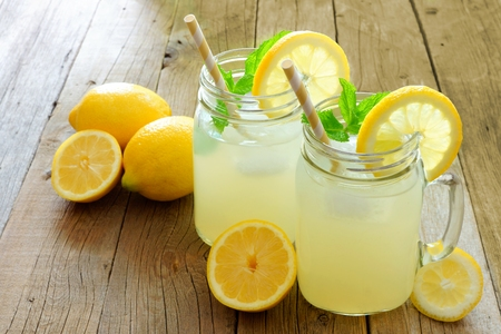 Two mason jar glasses of homemade lemonade on a rustic wooden background Reklamní fotografie