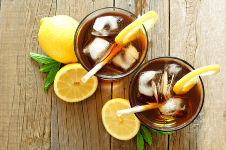 Two glasses of iced tea with lemon, overhead view on a rustic wooden background 스톡 콘텐츠