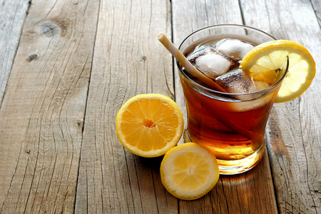 Glass of homemade lemon iced tea with straw on a rustic wooden background