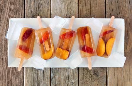 paletas de hielo: Melocotón helado paletas de té con cubos de hielo en la placa blanca y el fondo de madera rústica Foto de archivo