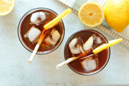 Two glasses of iced tea with lemons, overhead view on a white marble background