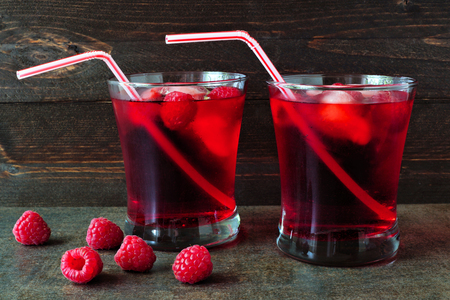 bendable: Raspberry fruit drinks in glasses with bendy straws over a dark background