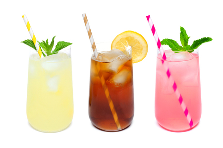 Three rounded glasses of summer lemonade, iced tea, and pink lemonade drinks with straws isolated on a white background Foto de archivo