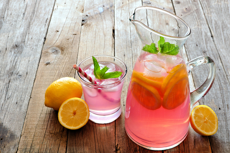 Pitcher of fresh pink lemonade with filled glass on a rustic wooden background