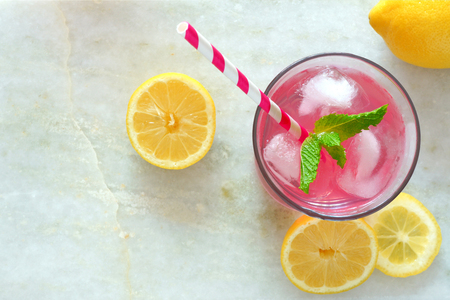 Glass of pink lemonade with mint and lemon slices overhead view on a white marble background