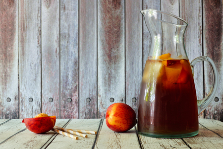 Pitcher of peach iced tea with fruit slices against a rustic wooden background