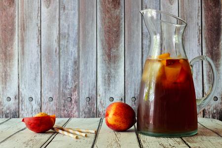 水蜜桃冰茶与水果片,以乡村的木制背景