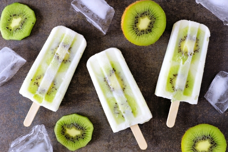 Kiwi vanilla yogurt popsicles with ice and sliced fruit on a dark stone background