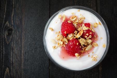 vegetarian food: Raspberry flavored Greek yogurt with granola, overhead view on dark wood