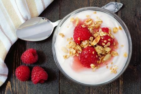 yogur: Raspberry flavored Greek yogurt with granola, overhead scene with spoon on dark wood