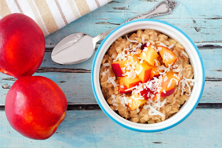 overnight: Bowl of overnight breakfast oats with diced peach and coconut, overhead scene on rustic blue wood