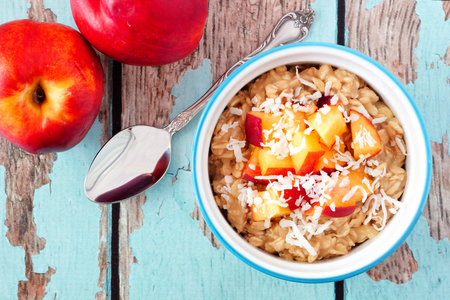 overnight: Bowl of overnight breakfast oats with diced peach and coconut, overhead scene on rustic wood
