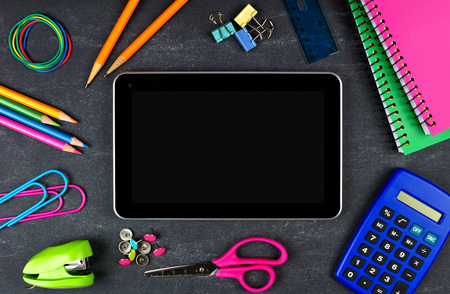 Blank tablet with frame of school supplies over a chalkboard background