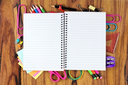 underlying: Blank opened lined school notebook with underlying frame of school supplies over a wooden desk background