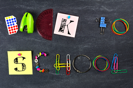 BACK TO SCHOOL spelled with school supplies against a blackboard background