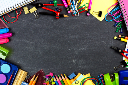 school board: Frame of assorted school supplies on a chalkboard background Stock Photo
