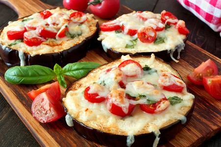 とろけるモッツァレラチーズ、トマト、バジルと健康的な茄子ミニピザをパドルボードにクローズ アップ 写真素材