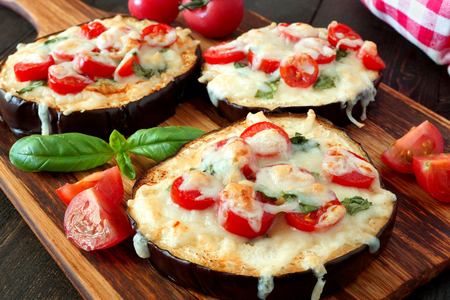 Healthy eggplant mini pizzas with melted mozzarella, tomatoes and basil, close up on a paddle board