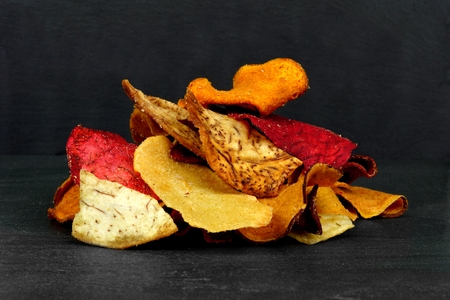 Pile of colorful organic vegetable chips on a black slate background