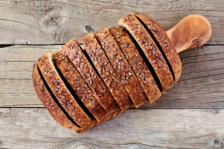 organic flax seed: Loaf of sliced whole grain bread with flax seeds, above view on wooden background Stock Photo