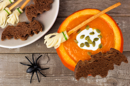 broomsticks: Halloween pumpkin soup with witchs broom and bat bread snacks on a rustic wooden background Stock Photo