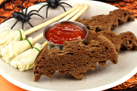 broomsticks: Halloween party food with bat breads and cheesy witchs broomsticks, close up table scene