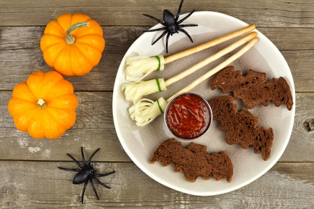 broomsticks: Halloween party food with bat breads and witches brooms, overhead scene on rustic wood