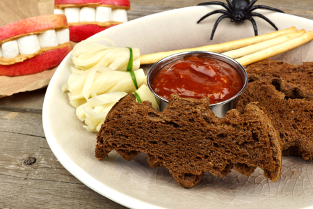 broomsticks: Halloween party food with bat breads, cheesy witchs broomsticks and apple teeth, close up table scene Stock Photo