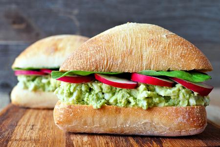 huevo blanco: Healthy avocado, egg salad sandwiches with radish slices and spinach on a ciabatta bun