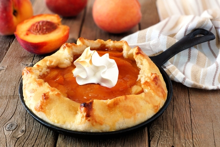 Peach tart with whipped cream in a cast iron baking skillet against a rustic wood background