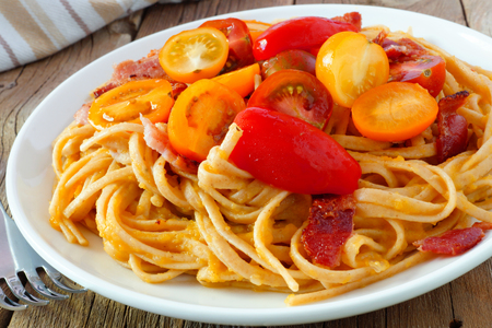 tomato sauce: Creamy butternut squash pasta dish with bacon and cherry tomatoes, close up on wood table