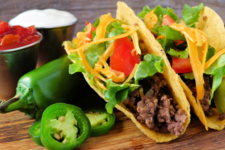 ground beef: Hard shelled tacos with ground beef, lettuce, tomatoes and cheese close up, on rustic wood Stock Photo