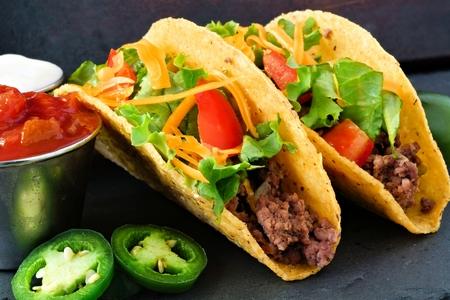 tortilla de maiz: tacos de cáscara dura con carne de res molida, lechuga, tomate y queso de cerca, en el fondo de la pizarra Foto de archivo