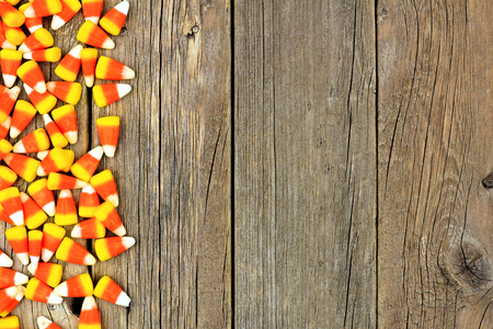 Halloween candy corn side border against a rustic wood background