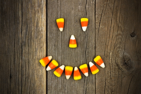 Halloween Jack o Lantern face made of candy corn over a rustic wooden background