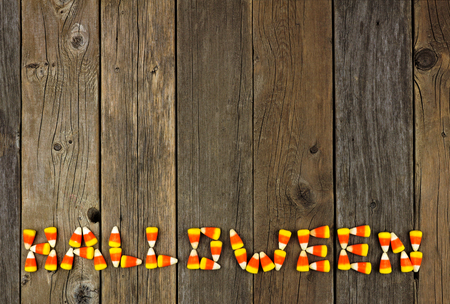HALLOWEEN written with candy corn over a rustic wooden background