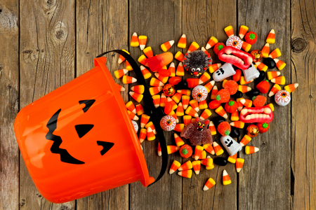Halloween Jack o Lantern pail with spilling candy, above view on a rustic wood background Stock Photo