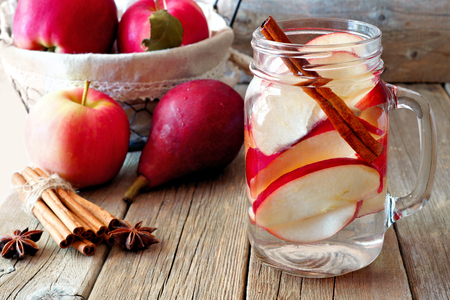 Autumn themed detox water with apple, cinnamon and red pear in a mason jar. Scene on rustic wood background 版權商用圖片