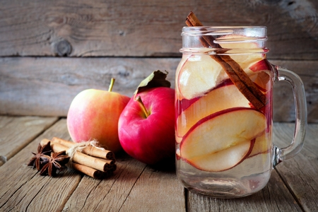 Autumn themed detox water with apple, cinnamon and red pear in a mason jar on a rustic wood background Banco de Imagens - 62560615