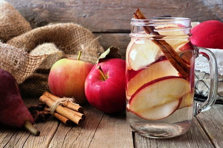 infused: Autumn themed detox water with apple, cinnamon and red pear in a mason jar. Scene on rustic wood background Stock Photo