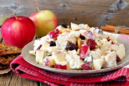 Autumn salad dish with chicken, apples, nuts and cranberries over rustic wood background