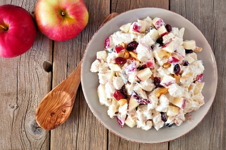 Autumn salad dish with chicken, apples, nuts and cranberries, above on rustic wood background