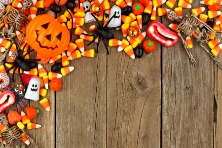 Halloween candy and decor top corner border against a rustic wood background