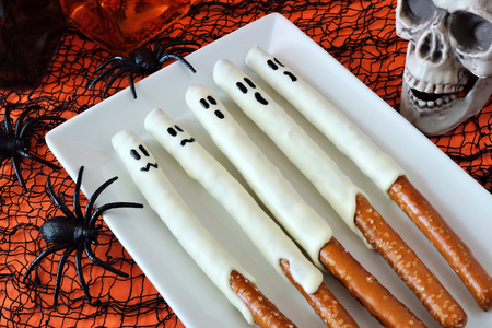 Spooky Halloween ghost candy dipped pretzel rods with decor, close up on a plate